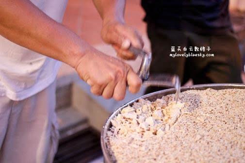 马来西亚老行业叮叮糖用铁锤和铁片敲打